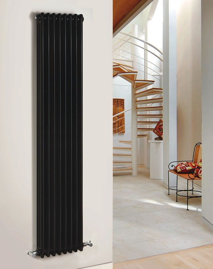 vertical black cast iron radiator on white wall