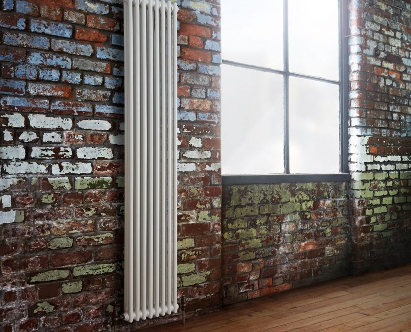 white radiator on brick wall