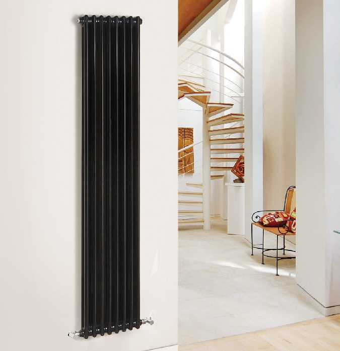 black vertical cast iron radiator on white wall