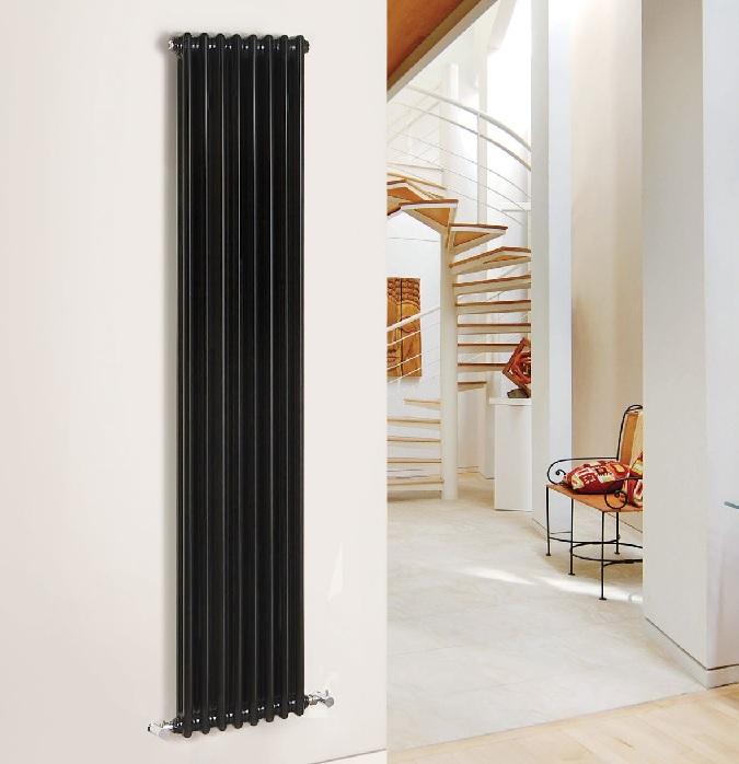 black vertical cast iron radiator on white wall